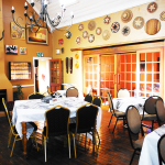 The character indoor dining area at Wakkerstroom Country Inn also has a roaring fireplace ideal for chilly winter nights and a cosy setting to enjoy with friends.